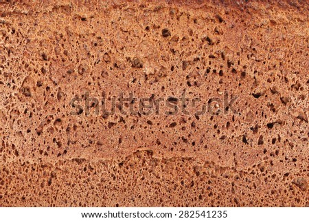 Surface of brown rye bread, close up, bread texture