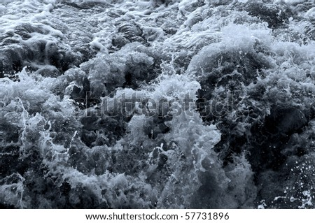 Surface of the water with waves and foam - stock photo