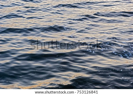 Surface of water with waves background texture, clear blue water in a lakesea with a wave, dark blue sea wave close up, azure water, glare of light on the water