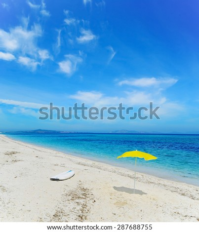 surfboard and beach umbrella on the sand