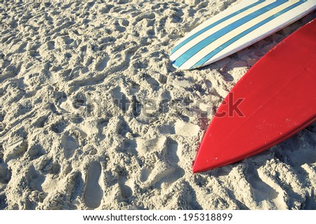 Surfboard and stand up paddle long board in bright red and blue stripes on Copacabana Beach Rio de Janeiro - stock photo