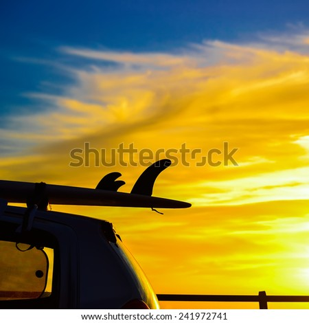 surfboard on a car roof at sunset. Shot in Sardinia, Italy - stock photo