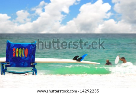 Surfboard on beach chair overlooking pretty ocean and swimmers