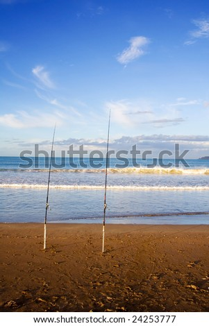 Surfcasting rods in the sand at Taipa Beach on a beautiful summers evening, Northland, New Zealand - stock photo