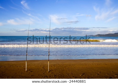 Surfcasting rods in the sand at Taipa Beach on a beautiful summers evening, Northland, New Zealand, - stock photo