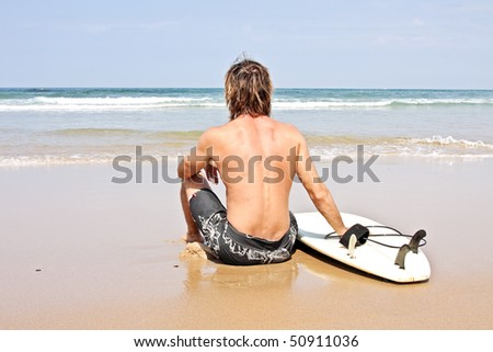 Surfer and his surfboard at the beach ready to surf - stock photo