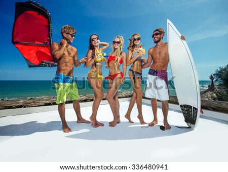 Surfer and kiter boys with beautiful girls group stay on beach  - stock photo