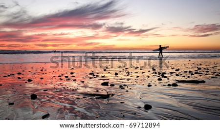 Surfer at sunset - stock photo