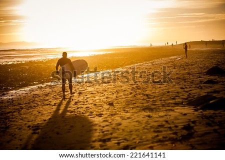 Surfer at the beach at sunset - stock photo