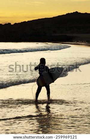 surfer boy on the seashore at sunset in Doninhos, Galicia Beach - stock photo