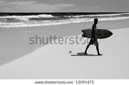 Surfer carrying board leaving pretty beach - stock photo