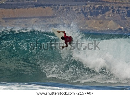 Surfer carving on a wave in El Confital in Las Palmas in Gran Canaria