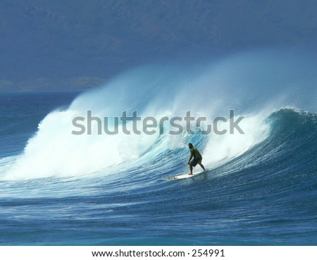 Surfer catches a good ride in Maui's heavy surf. - stock photo