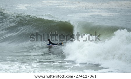 Surfer catching a wave - stock photo