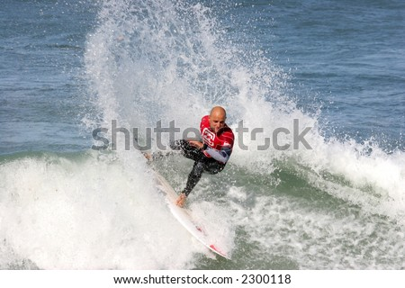 surfer catching a wave with a big round spray of water