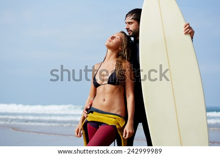 Surfer couple in love standing together on a beach holding a surfboard, romantic couple standing on the beach at sunny day - stock photo