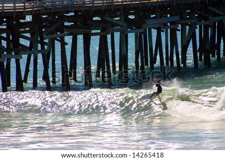 Surfer does a Cutback next to the San Clemente Pier - stock photo