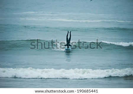 Surfer Doing Headstand on Wave - stock photo