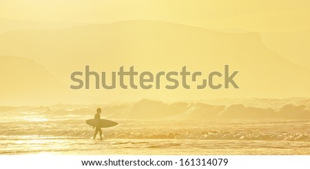 surfer entering water at sunset - stock photo