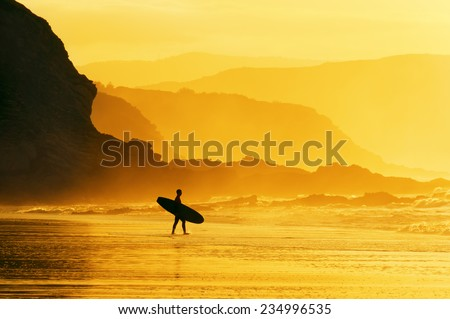 surfer entering water at the misty sunset - stock photo