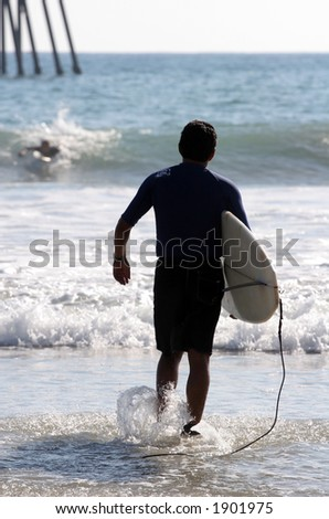 Surfer enters the ocean. - stock photo