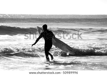 Surfer enters the water wearing a wetsuit - stock photo