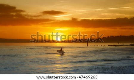 Surfer finishing for the day as the sun sets - stock photo