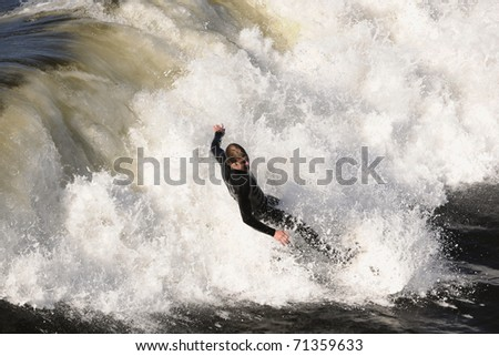 Surfer gets up on a wave. The wave twists with foam and splashes. - stock photo