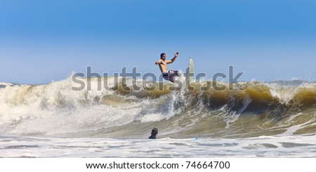 surfer getting air on big waves - stock photo