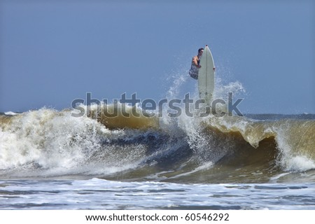 surfer getting big air and wiping out in rough atlantic surf - stock photo