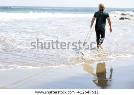 Surfer getting in the water in Malibu - stock photo