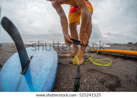 Surfer getting on the surfboard's leash