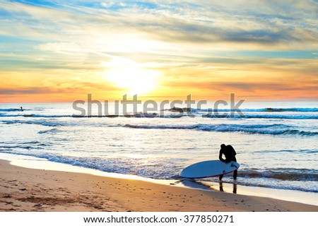 Surfer getting ready for surfing on the beach at sunset - stock photo
