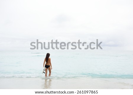 Surfer girl going surfing looking at ocean beach. Female bikini woman heading for waves with surfboard having fun living healthy active lifestyle. Water sports with model. - stock photo