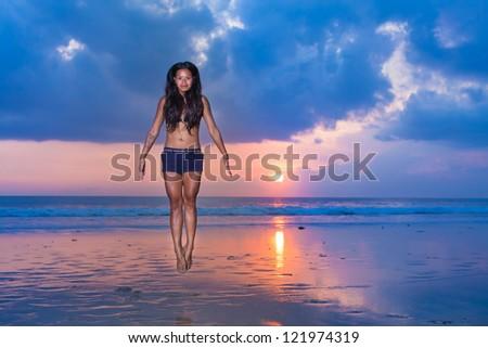 surfer girl levitating on the beach - stock photo