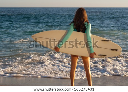 Surfer girl on the beach - Female surfer standing on the beach surfboard in hand with the ocean in the background. - stock photo