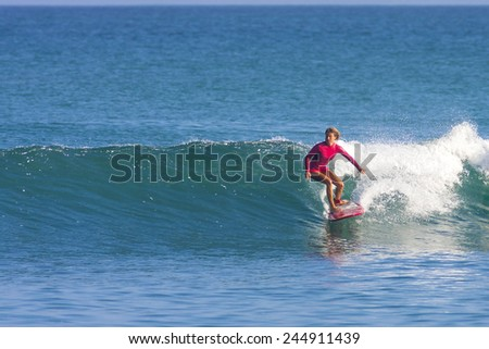 Surfer girl on the wave, Indonesia. - stock photo