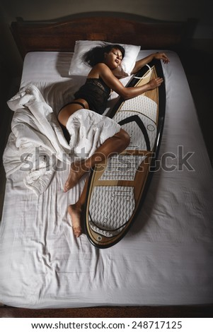 Surfer girl sleeping in bed - stock photo