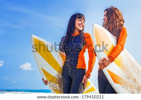 Surfer girls discussing something and smiling - stock photo