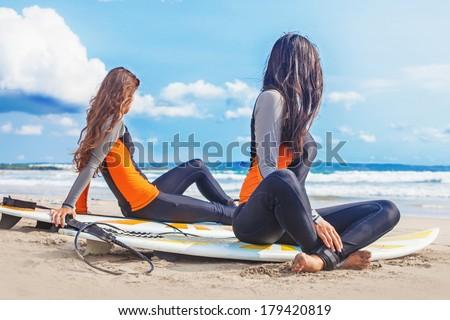 Surfer girls relaxing near the ocean - stock photo