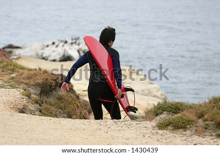 Surfer going down to the waves - stock photo
