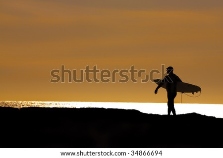 surfer heading out in the setting sun for a final ride at Santa Cruz, CA - stock photo
