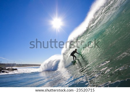 Surfer in Perfect Tube with Sun - stock photo