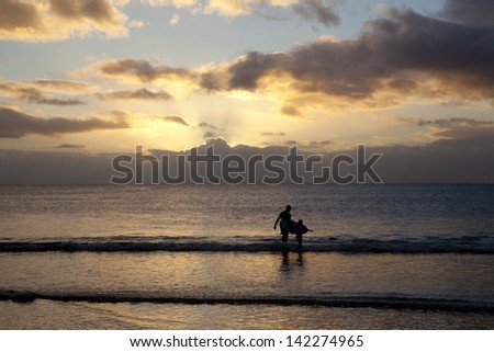 Surfer in sea on Mauritius island at sundown - stock photo