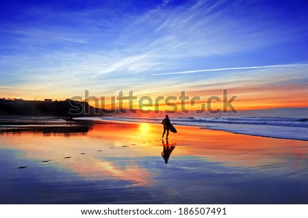 surfer in the beach at sunset - stock photo