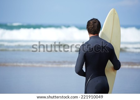 Surfer in wetsuit holding a surfboard and waiting the waves, beautiful brunette surfer man holding his surfing board standing against ocean with big waves, healthy lifestyle concept - stock photo