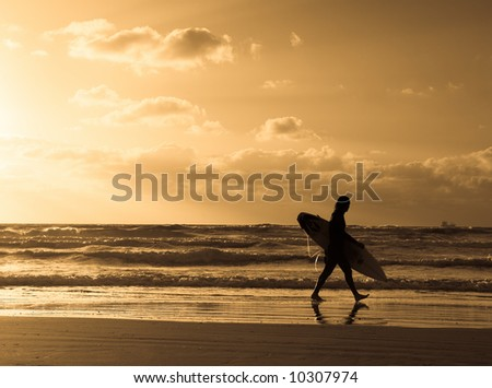 Surfer is walking along Israel's shore and big sun coming out from the clouds, sepia and high contrast.