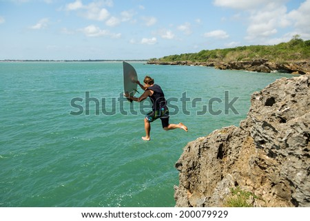 surfer jumps off a cliff into the ocean - stock photo