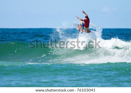 surfer jumps over the big wave with a splash - stock photo
