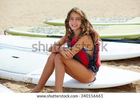 Surfer kid girl sitting in surfboard on the beach sand - stock photo